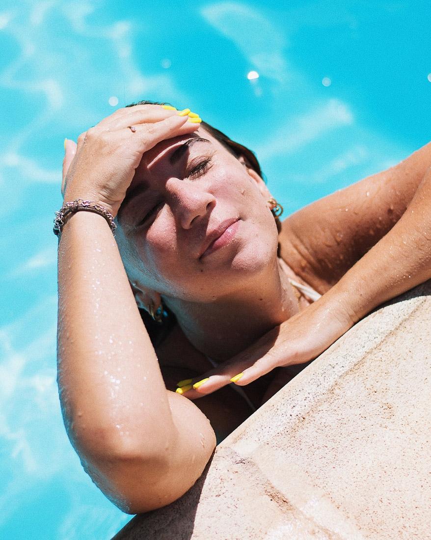 chica en la piscina tomando el sol